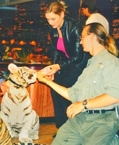 Kate Winslet feeding milk to a tiger cub.